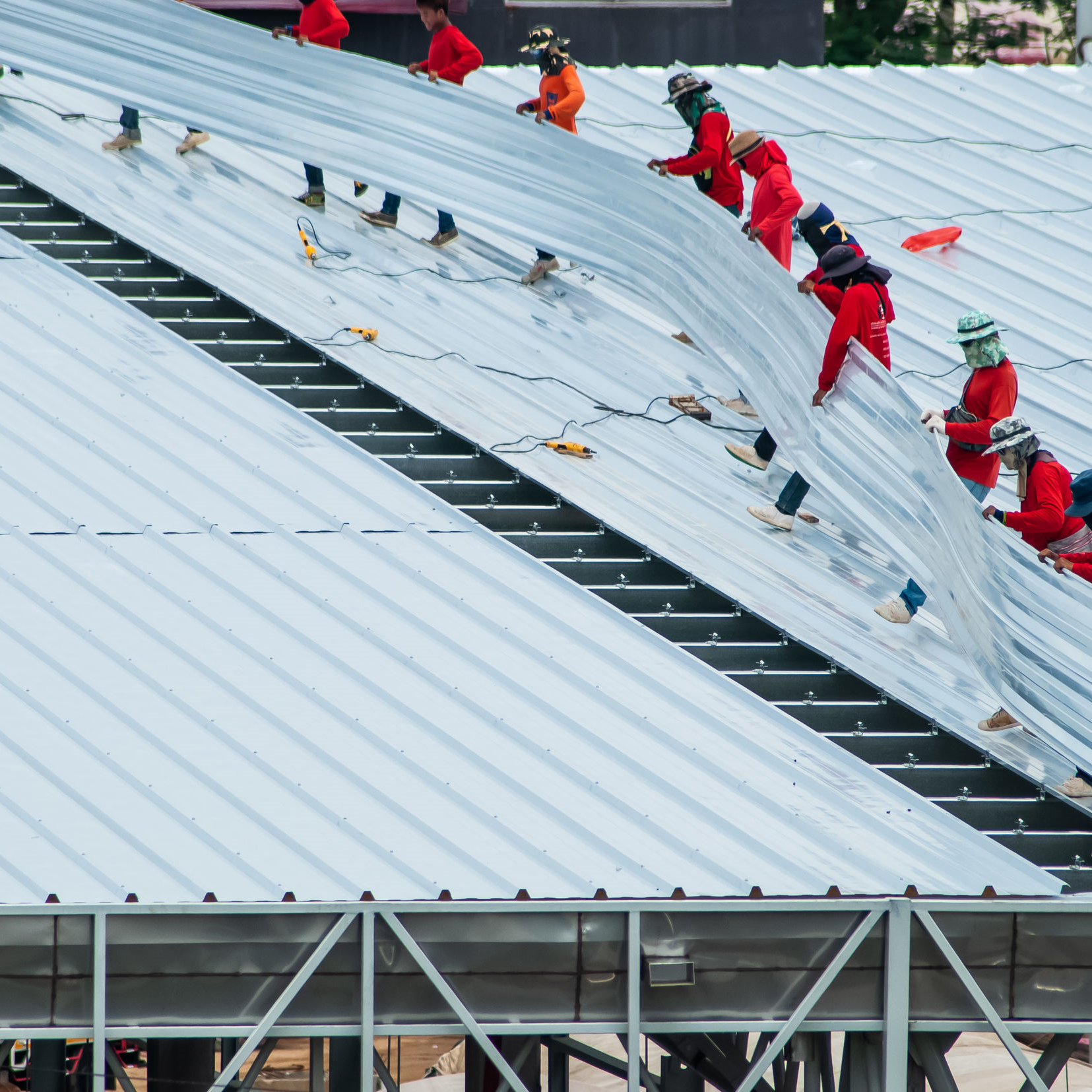 Roofers installing a commercial metal roof.