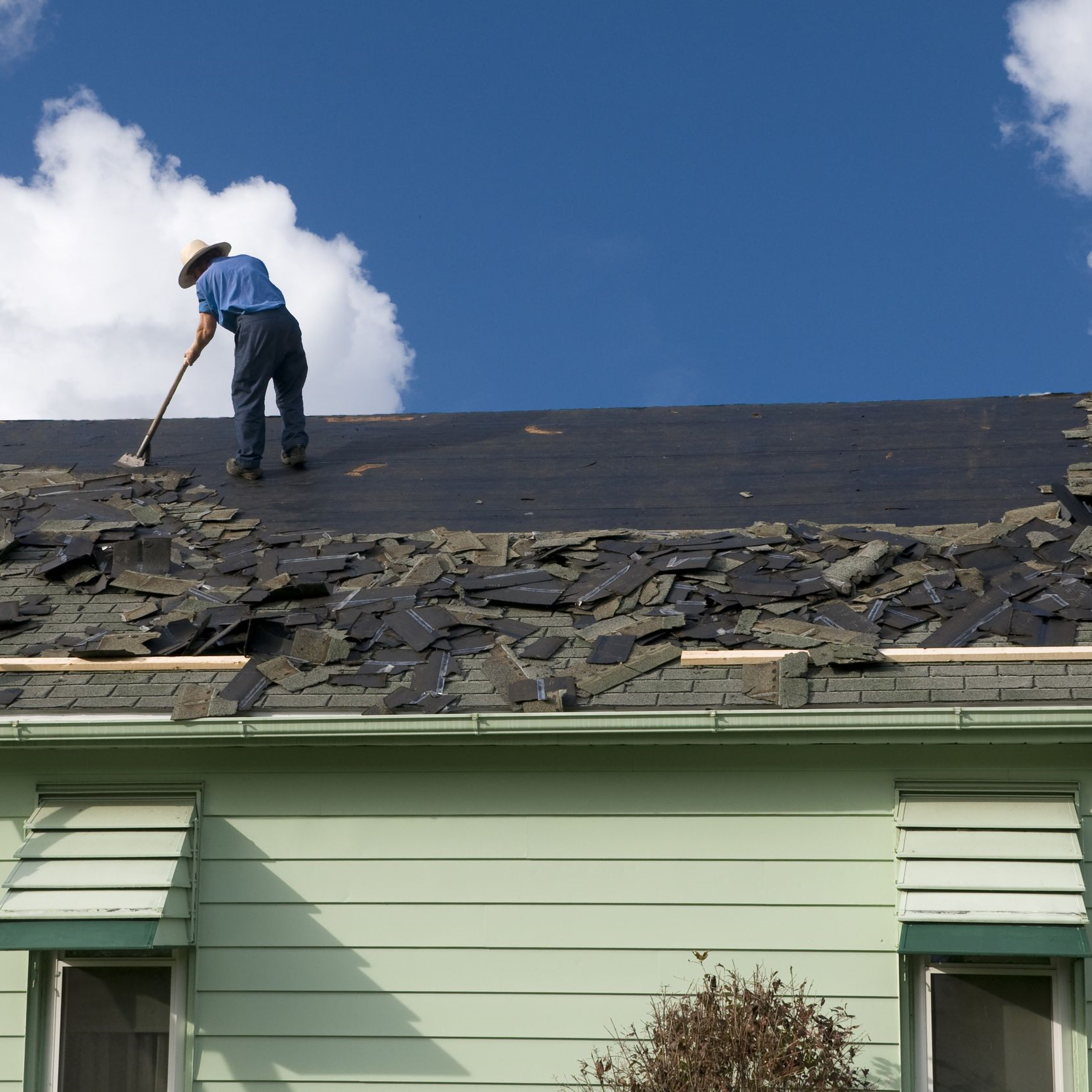 Roofer removing damaged shingles before replacement.