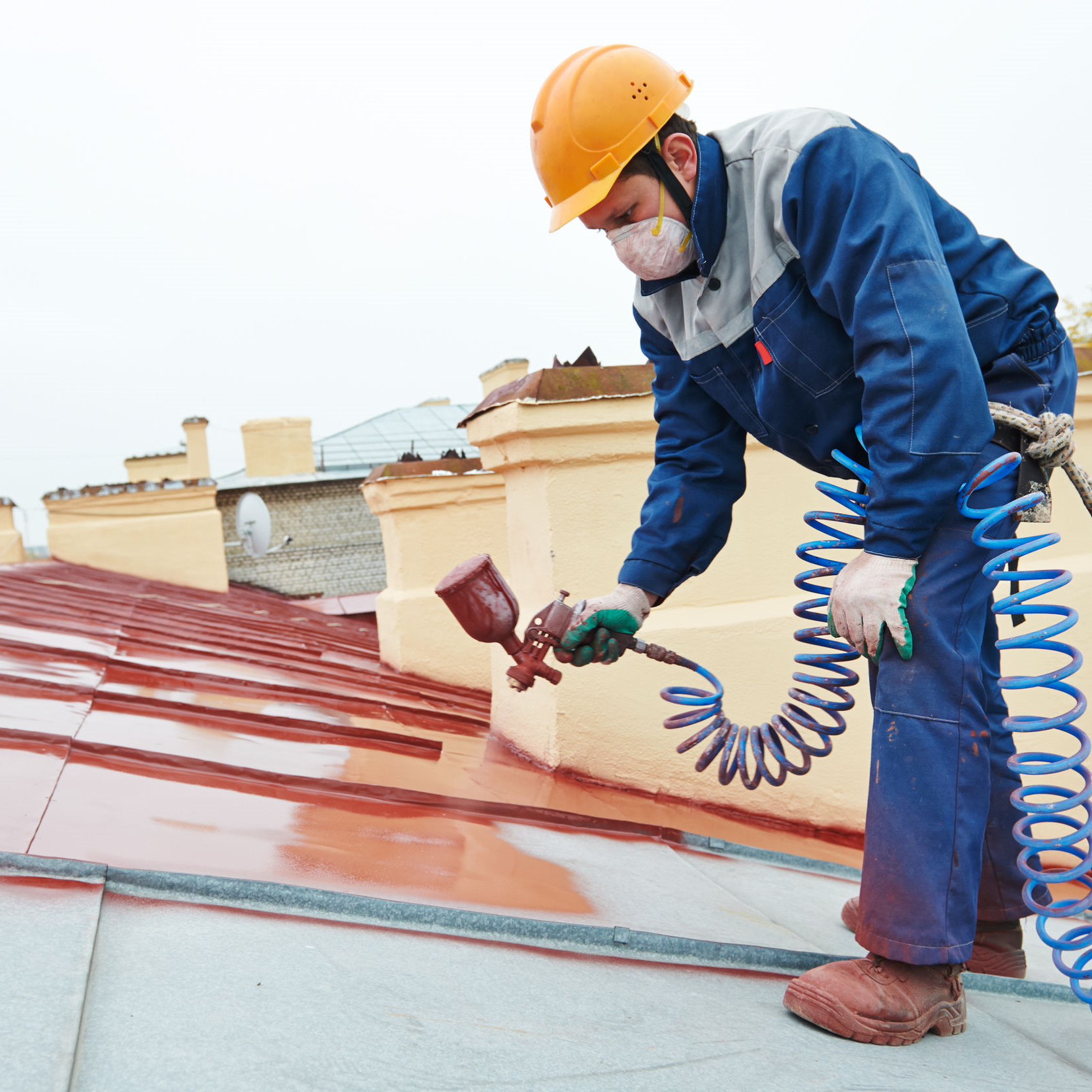 A roofer applying elastomeric coating to a metal roof.