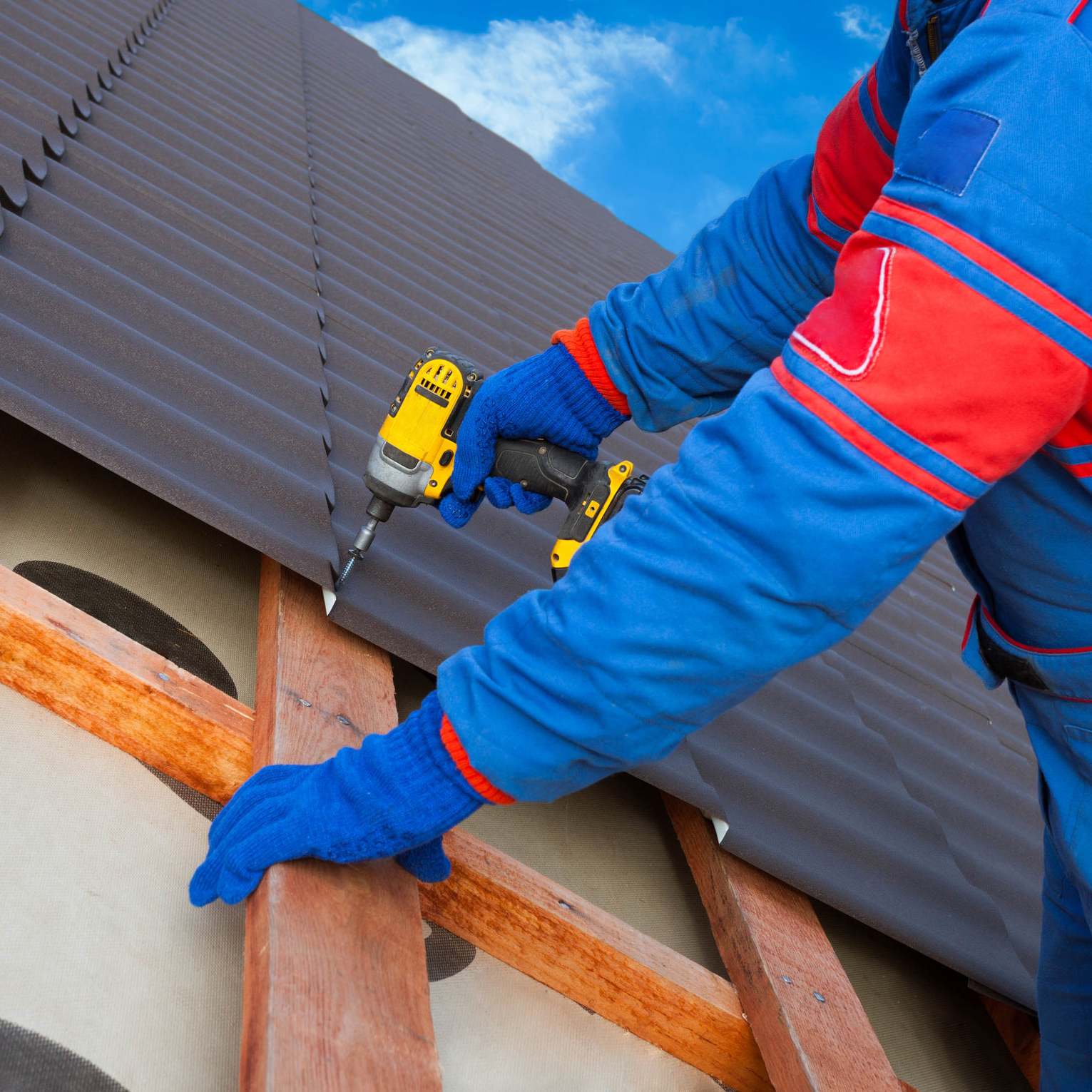 A roofer installing a metal roof