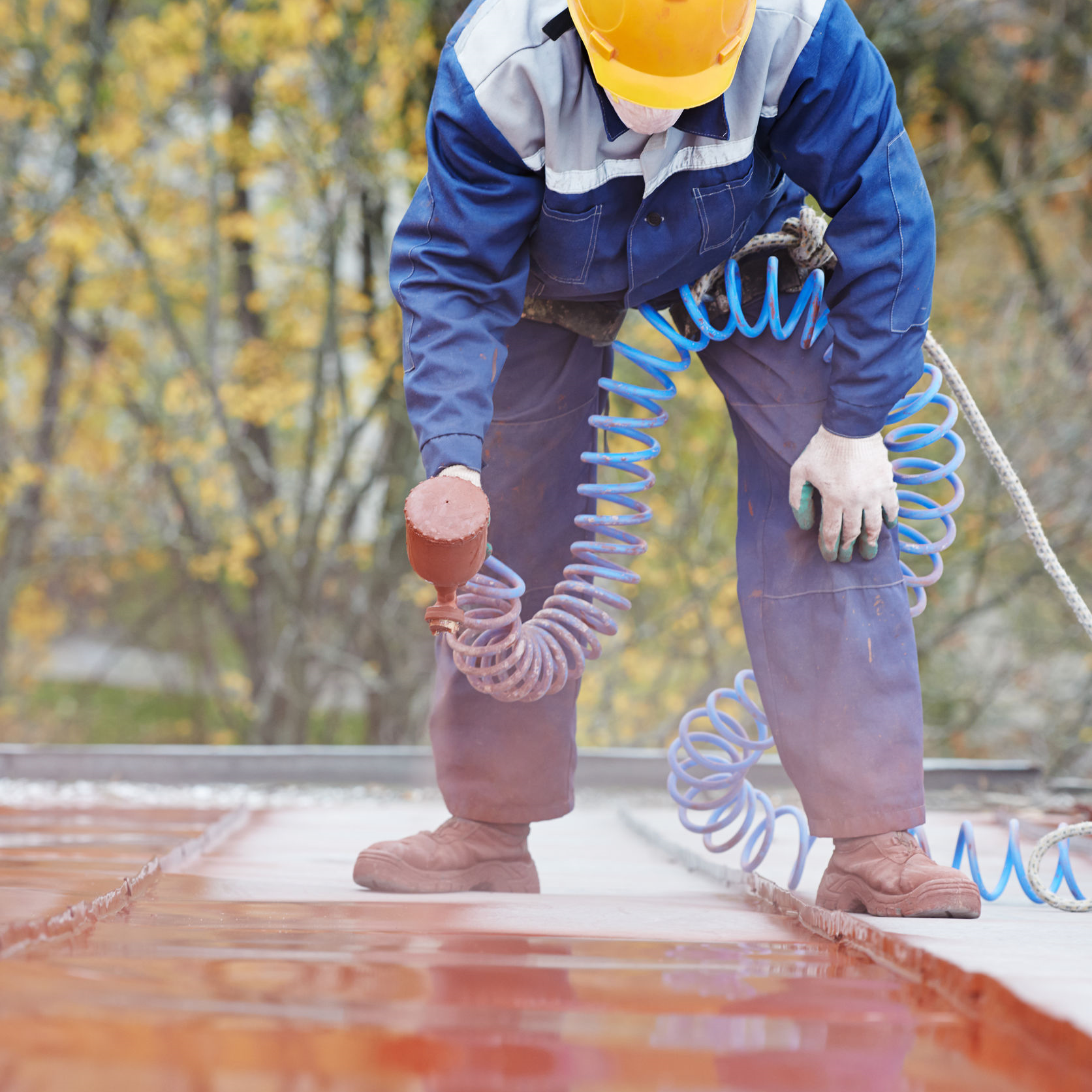A roofer applying metal roof coating