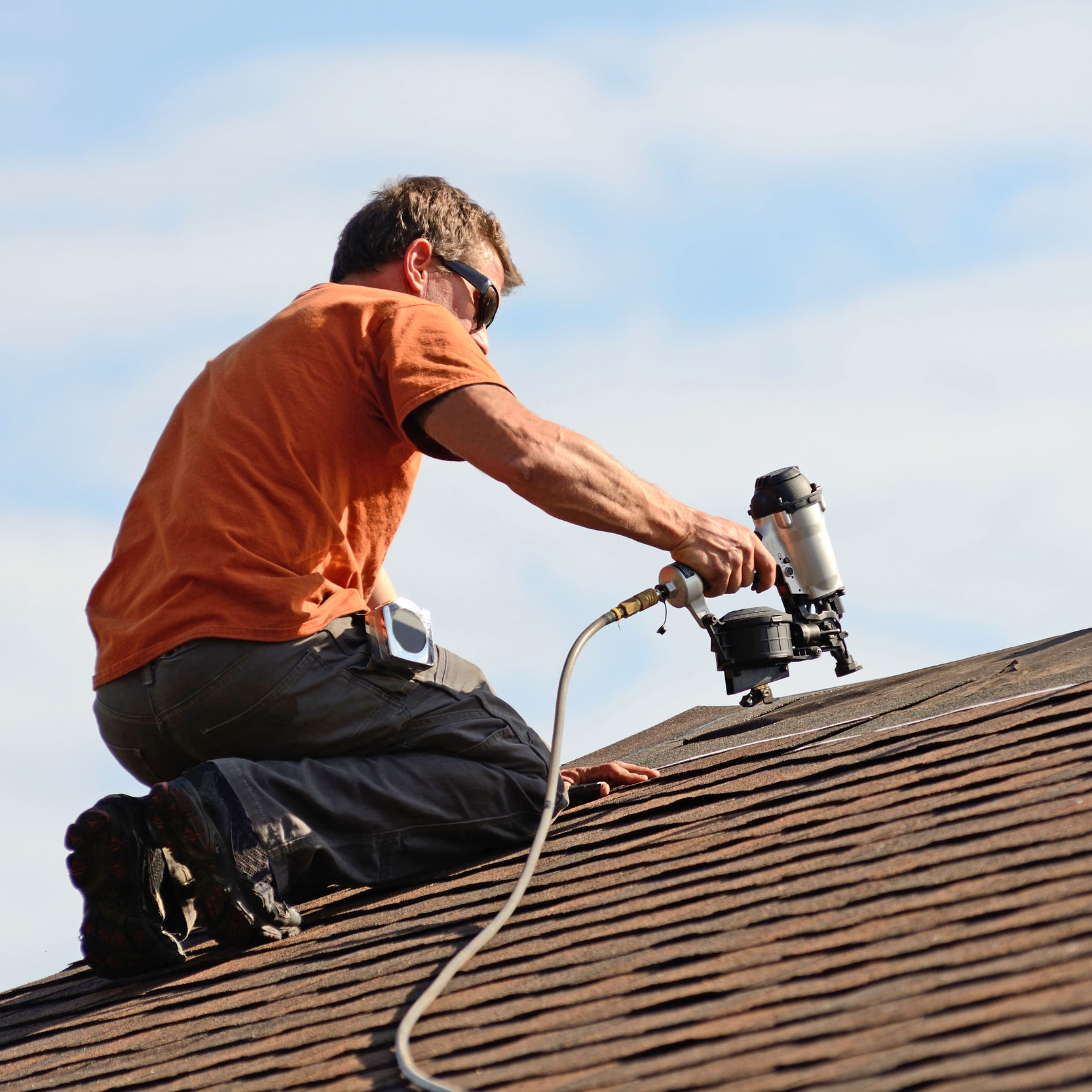 A roofer repairing a residential roof