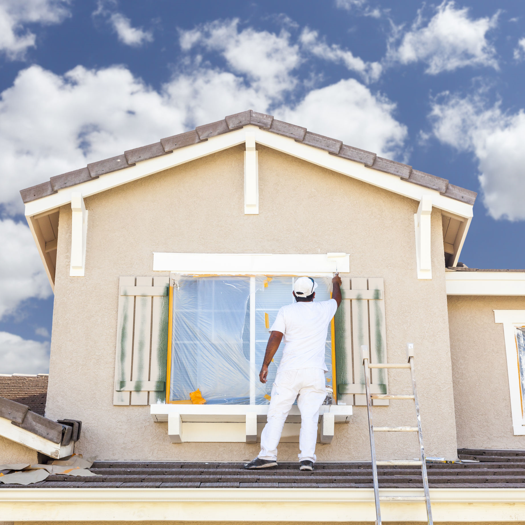 A painter painting a homes exterior.