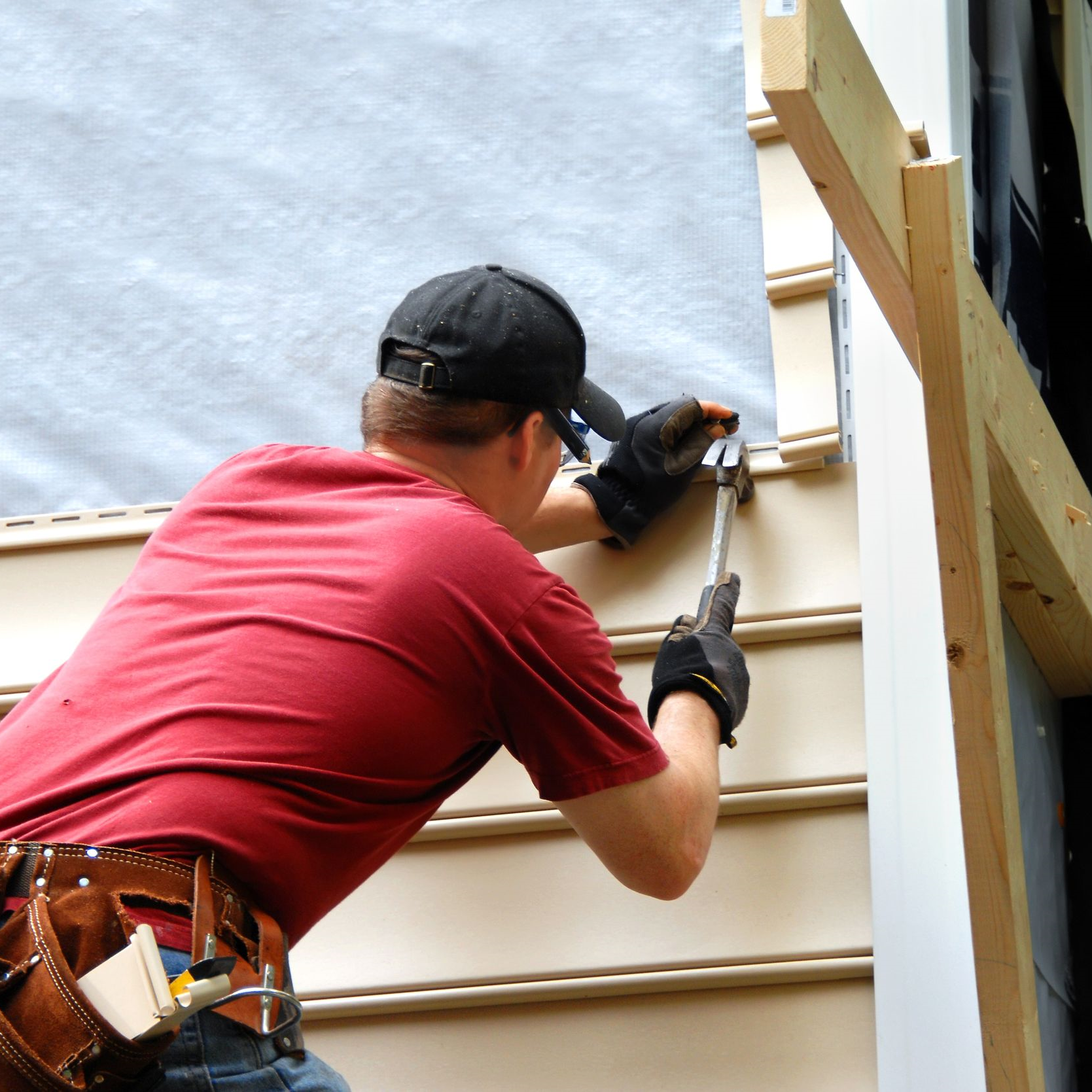 A roofer installing a siding